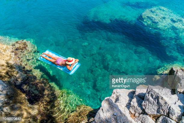 women is sunbathing on the seabed. - mugla province stock pictures, royalty-free photos & images