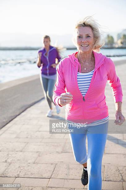 women jogging by beach - old women in pantyhose stock photos and pictures