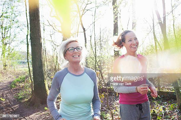 Women jogging in forest smiling