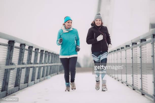 Women jogging on a snow covered path