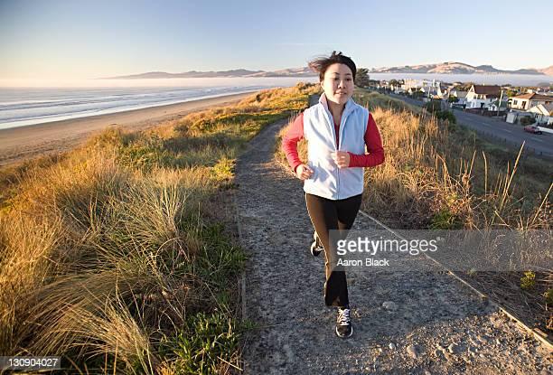 women jogging on path near beach in sun