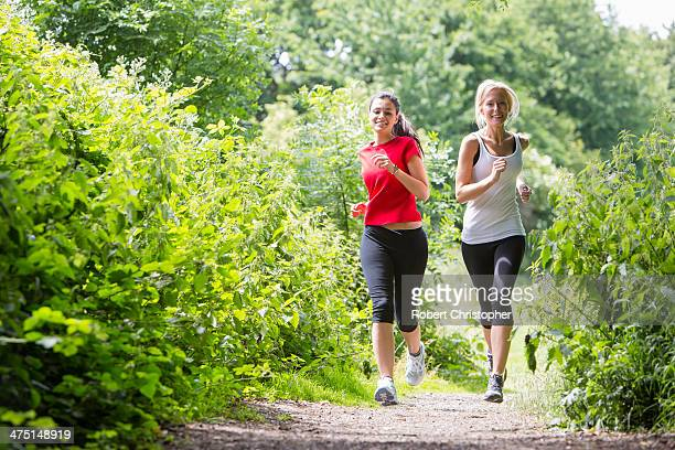 Women jogging through forest