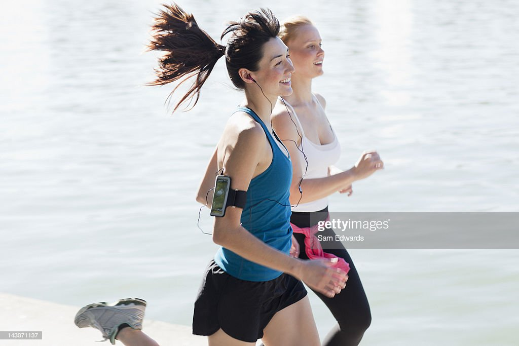 Women jogging together by lake : Stock Photo