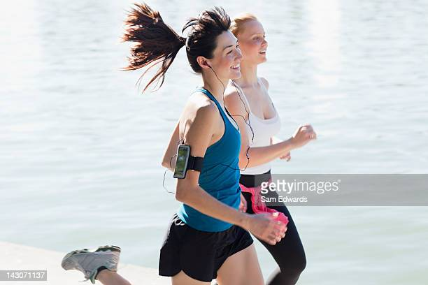 Women jogging together by lake