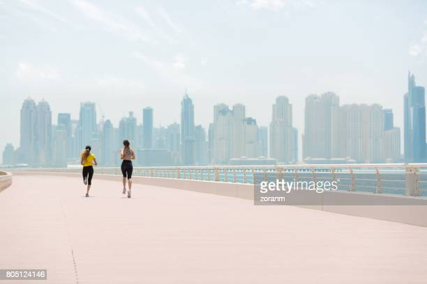 Women jogging with cityscape in background