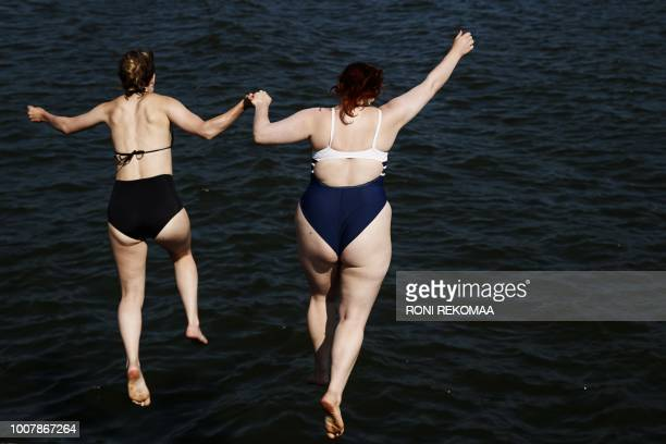 Women jump into the sea during a hot summer day in Helsinki on July 30 2018 / Finland OUT