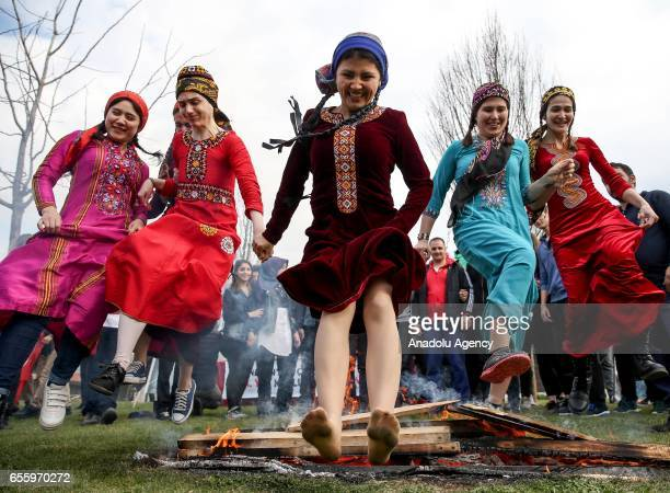 Women jump over a bonfire during the Newroz celebrations at Topkapi Culture Park in Istanbul Turkey on March 21 2017 Newroz is the March 21 festival...