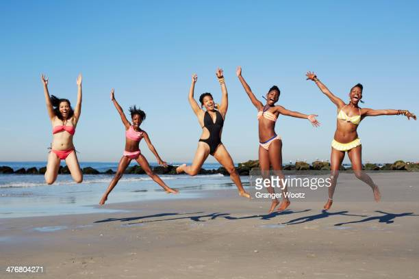 Women jumping for joy on beach