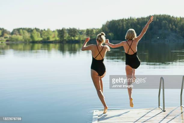 women jumping into lake from deck - sweden stock pictures, royalty-free photos & images