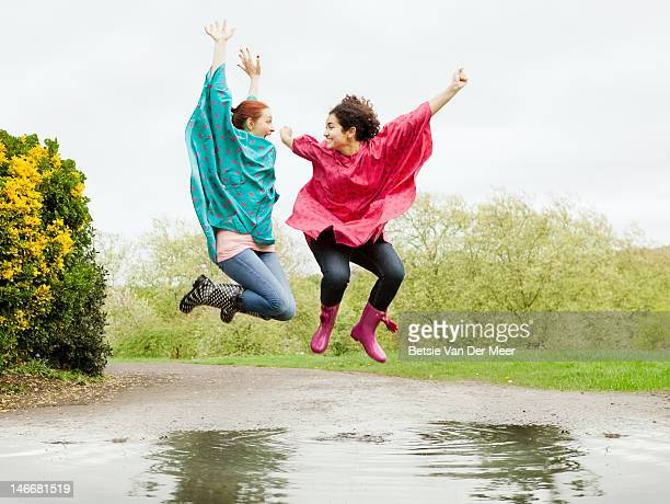 women Jumping mid air in large puddle