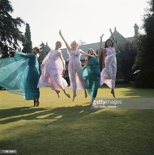 Women jumping on lawn