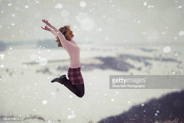 Women Jumping on top of Valley in Snow Storm