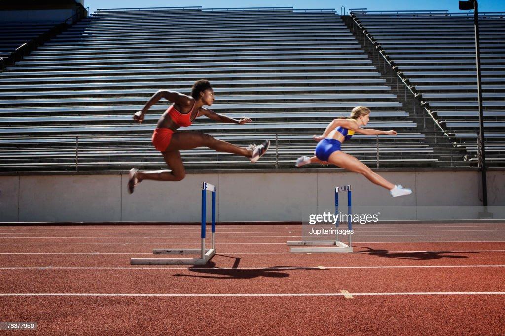 Women Jumping Over Hurdles