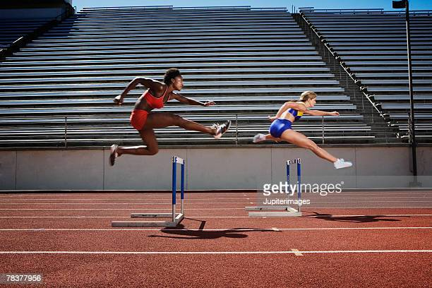 women jumping over hurdles - athletics stock photos and pictures