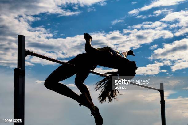 women jumping over the lath, silhouette - high jump stock pictures, royalty-free photos & images