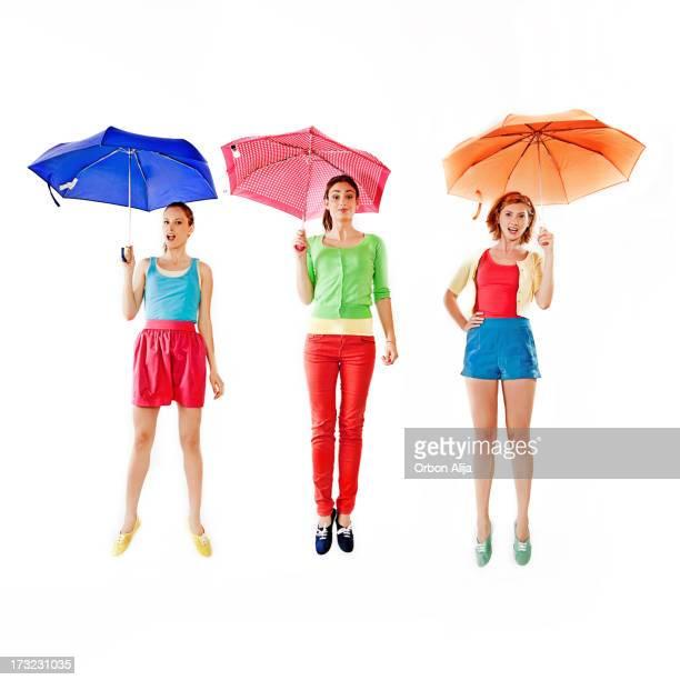 Frauen springen mit Regenschirm