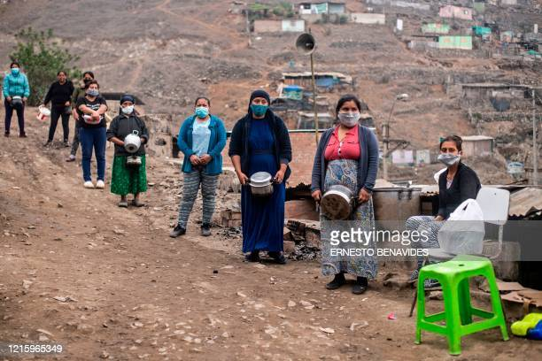 Women keep safety distances as they wait to get food at a soup kitchen of the Pamplona Alta section -which also suffers water shortage- in the...