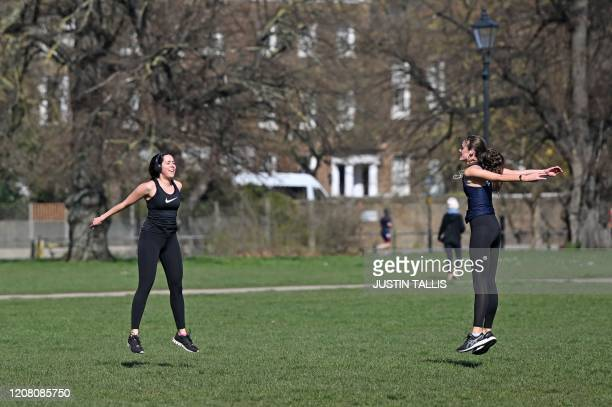 Women keep their distance from each other as they exercise on Clapham Common in south London on March 24 2020 after Britain's government ordered a...