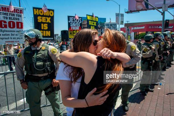 Women kiss in reaction to insults from an evangelical Christian preacher near counterprotesters during the annual LA Pride Parade in West Hollywood...