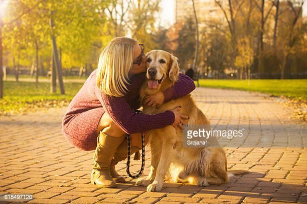 Women kissing golden retriever in autumn park