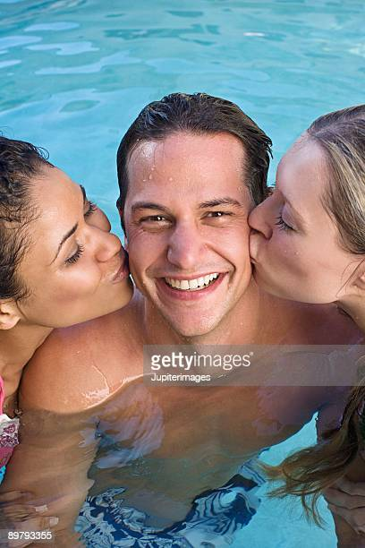 women kissing man on cheek in swimming pool - man met een groep vrouwen stockfoto's en -beelden