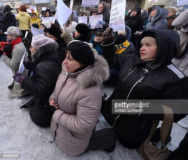 Women kneel in front of the police in Kiev on January 24 2014 Ukrainian protesters Friday expanded their protest camp in Kiev closer to the...