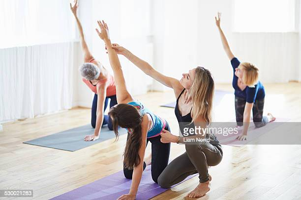 Women kneeling and raising arms in pilates class
