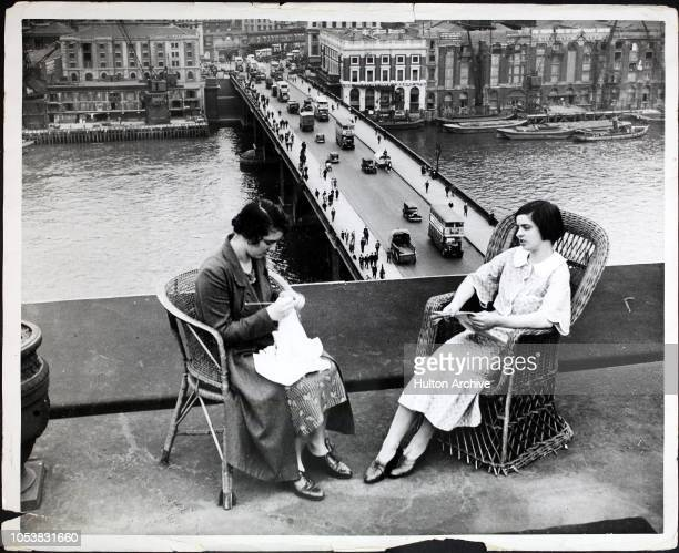 Women knitting and reading on a rooftop above London Bridge London England circa 1925