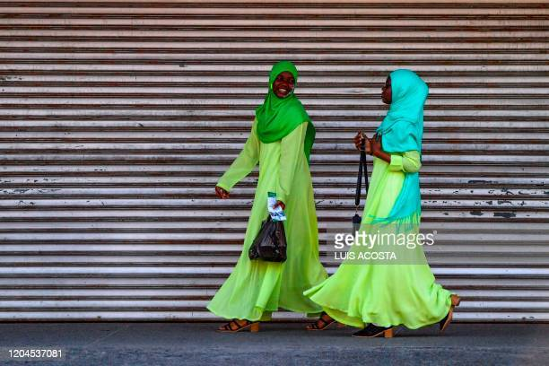 TOPSHOT Women laugh as they walk in Georgetown Guyana on March 1 2020 Guyana goes to the polls March 2 in a pivotal election in one of South...