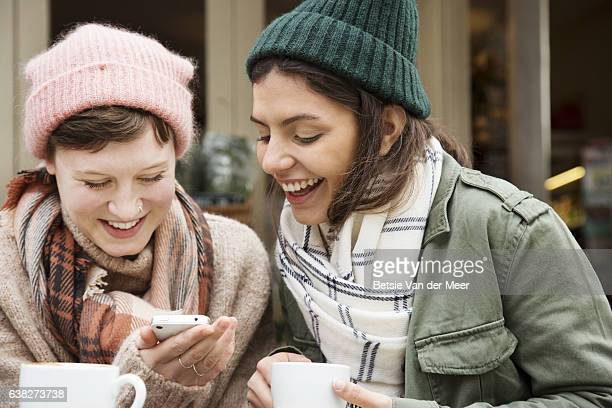 Women laughing and chatting while looking at phone in outdoor urban cafe.