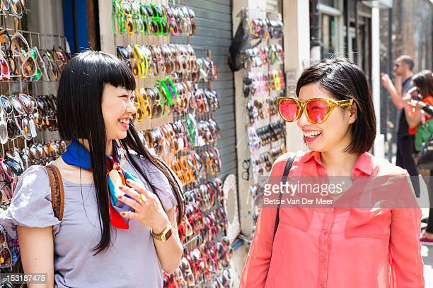 Women laughing at choice of large sunglasses.