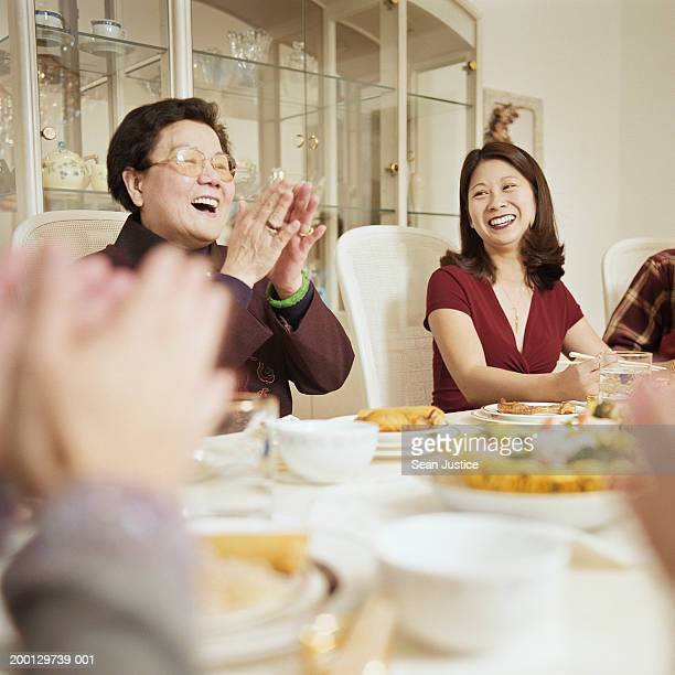 Women laughing at dinner table, grandmother clapping