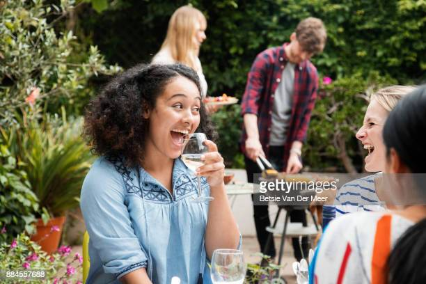 Women laughing, drinking wine, while friends prepare food on barbecue in background.