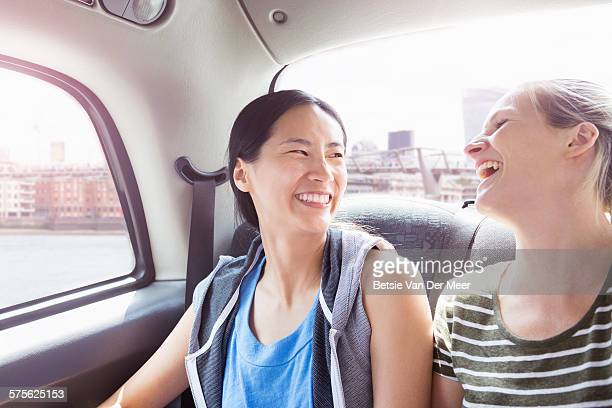Women laughing in back of cab