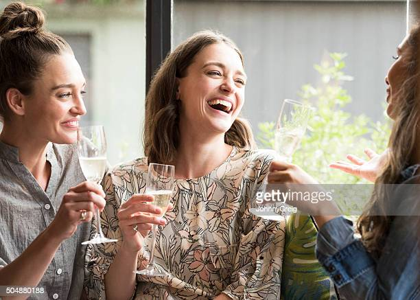 women laughing in bar with wine glasses - alcohol stock pictures, royalty-free photos & images