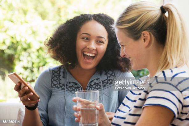 Women laughing looking at phone, sitting on sofa.