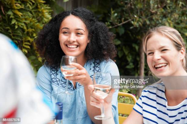 Women laughing, talking and drinking wine at barbecue party.