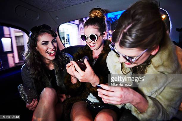 Women laughing together in taxi