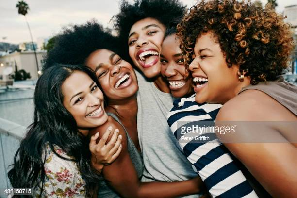 women laughing together on urban rooftop - nur frauen stock-fotos und bilder