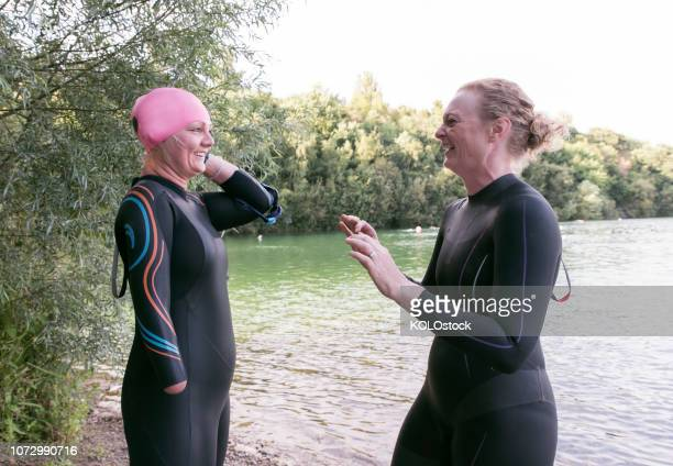 Women laughing while putting on swimming cap