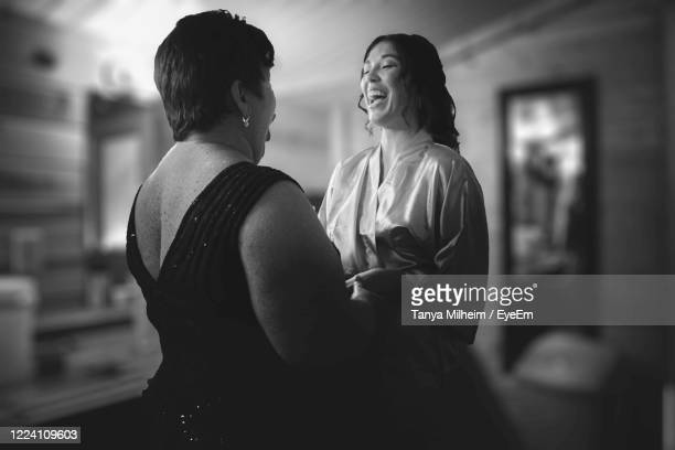 women laughing while standing at home - marriage stock pictures, royalty-free photos & images
