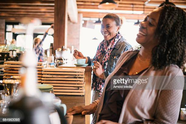 Women Laughing while waiting for their coffee