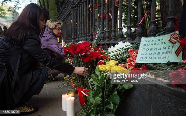 Women lay flowers by the fence of the Ukrainian embassy in Moscow on May 3 in honour of people killed during clashes in Odessa. Ukrainian soldiers...