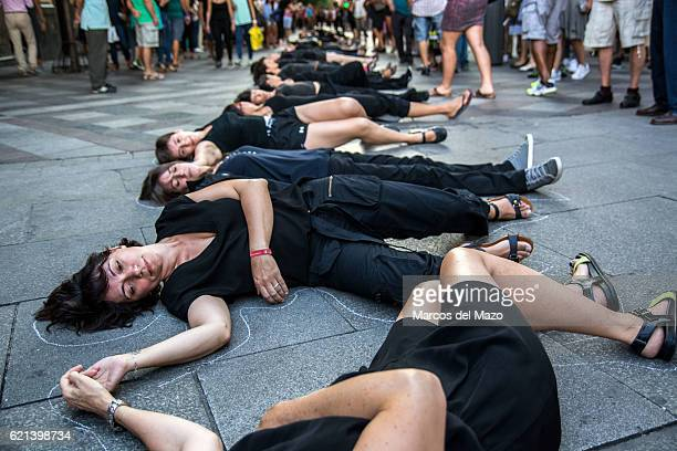 Women lay on the floor as if they were dead during a performance carried out by 'Women in Black' protesting in Madrid against genderbased violence