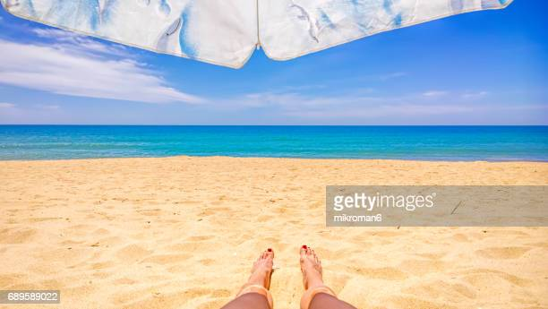 a women laying in faro beach on hot summer day. - faro city portugal stock photos and pictures