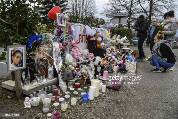 Women lays roses and people gather at a makeshift memorial in tribute to eightyearold Maelys de Araujo on February 15 2018 in Le PontdeBeauvoisin...