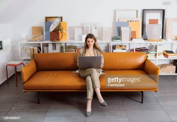 frauenführerinnen: eine geschäftsfrau im anzug, die auf einem sofa sitzt und an ihrem laptop in einem modernen büro arbeitet - designer einrichtung stock-fotos und bilder