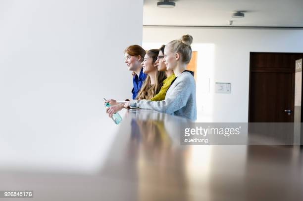 Women leaning on low wall