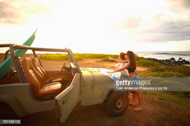 Women leaning on off-road vehicle with surfboard reading map