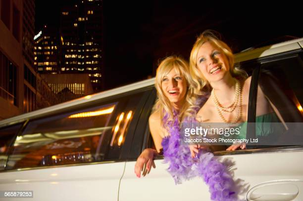 Women leaning out limousine window at night